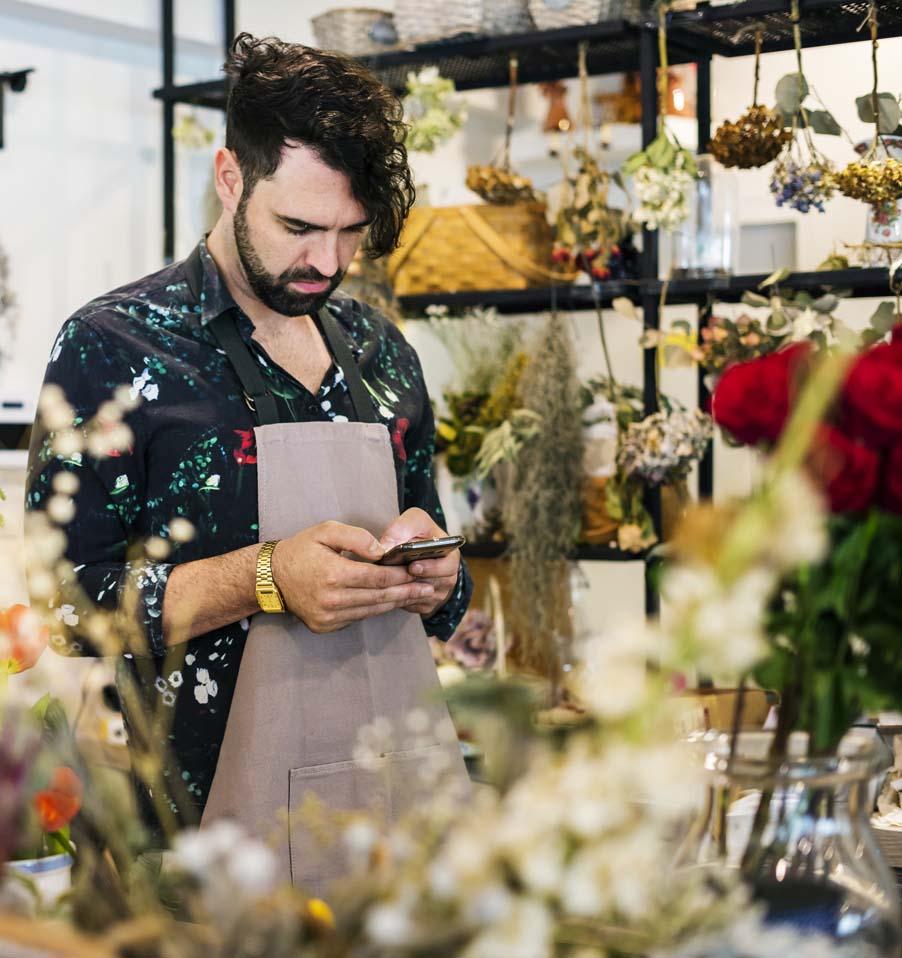 Florista hipster mirando el movil